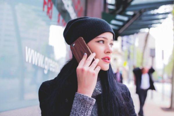 耳にスマホを当て電話をしている女性