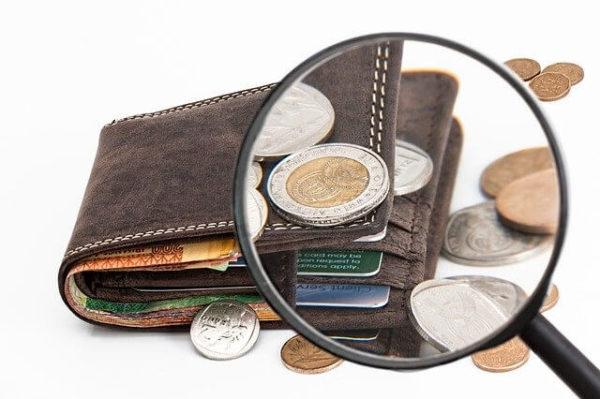 財布を虫メガネで見ている